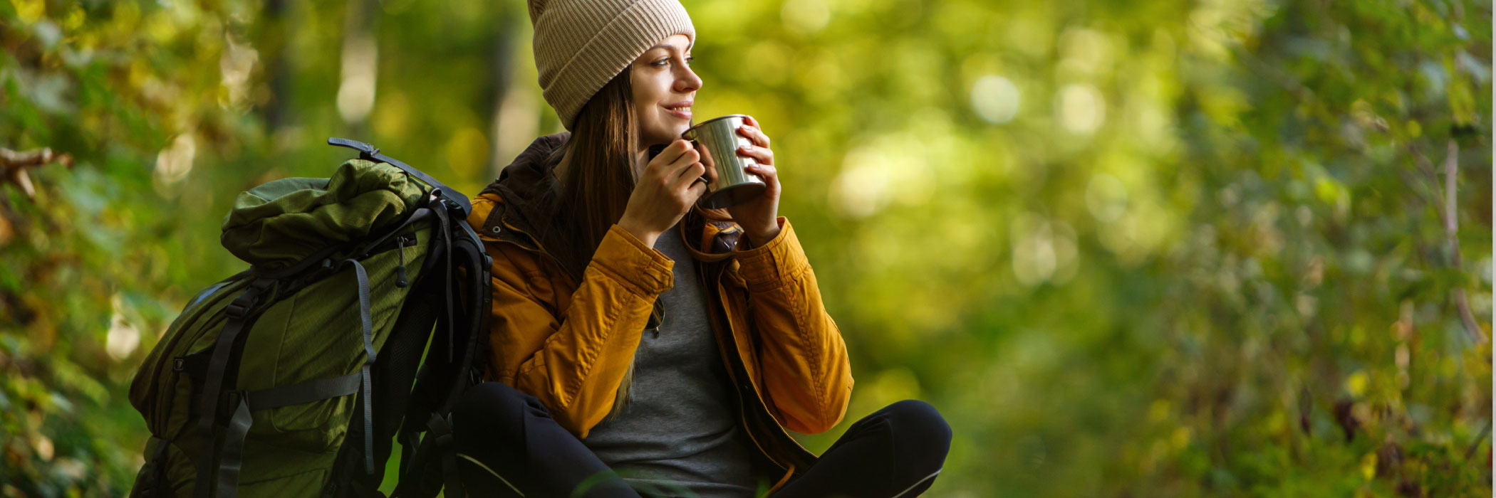 Woman with backpack sitting in forest enjoying a cup of tea