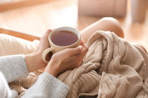 Woman holding a mug of tea on her lap