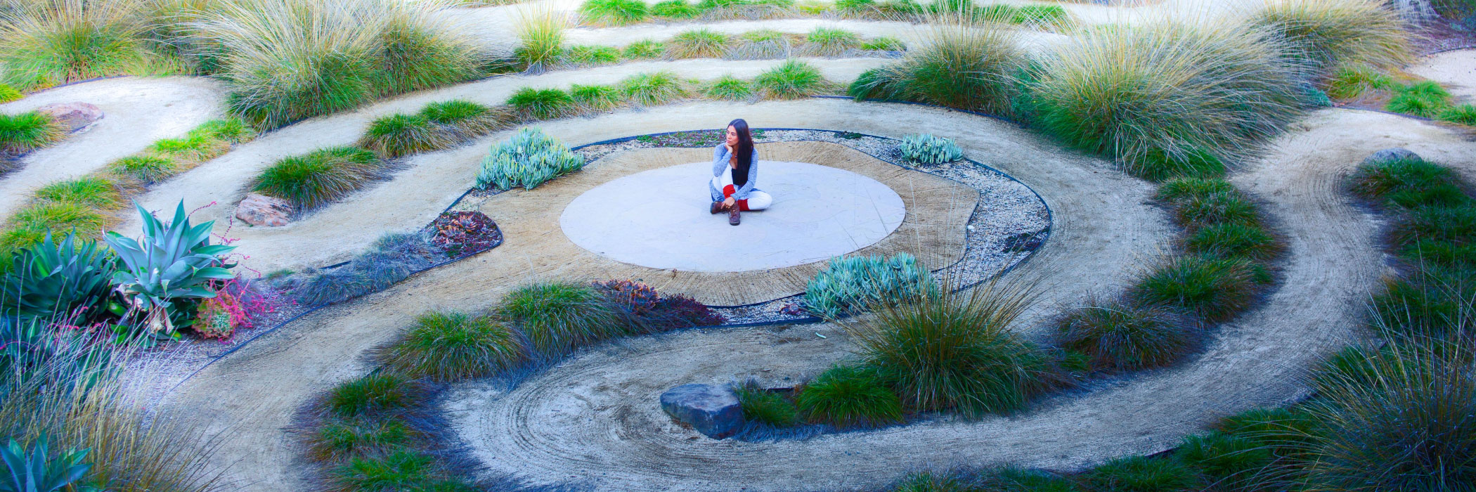 Woman sitting in the middle of a labyrinth of bushes