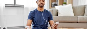 Man meditating with earphones connected to phone