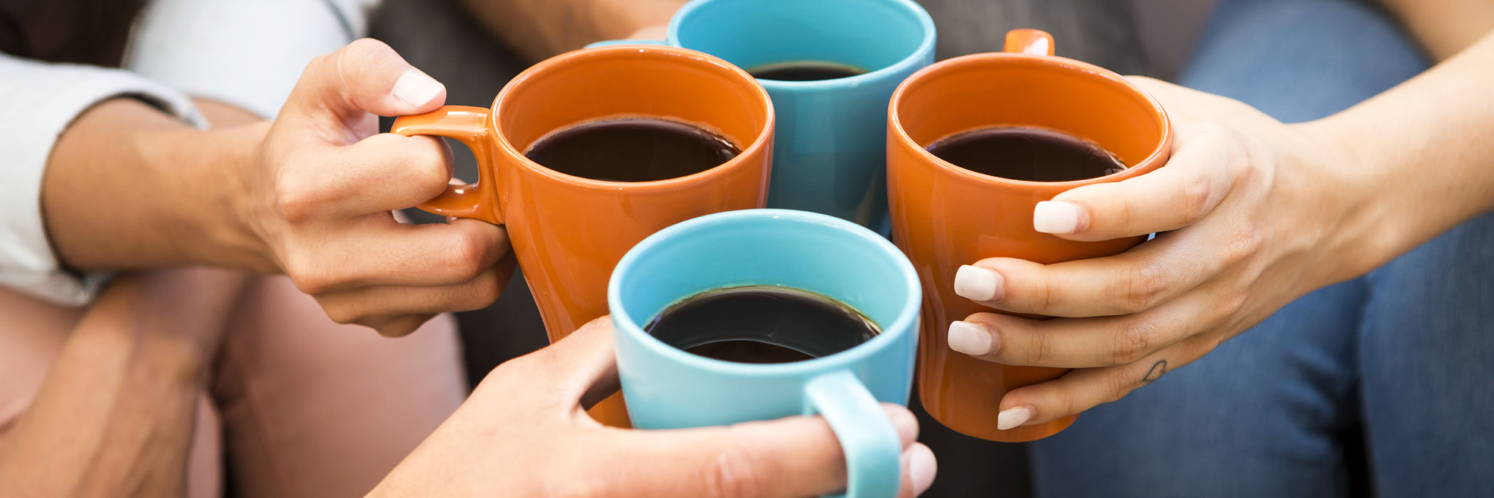 Four friends toasting mugs of coffee